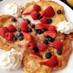 picture of apple pancakes with fresh fruit and whipped cream