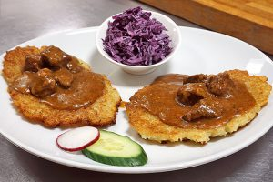 picture of beef goulash with potato pancakes and side salad