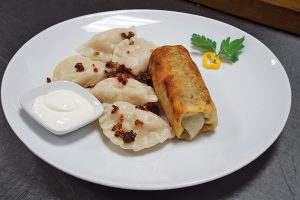 ensemble of 5 pierogi and 1 krokiet with sour cream on a side