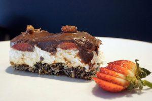 image of a cake made of coconut poppy seed, meringue custard cream, cookies soaked in liquid jello, and chocolate ganache
