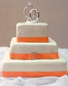 photo of a three tire cake with rings at the top