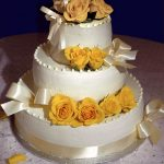 photo of a cake with yellow roses