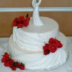 photo of a two tier cake with red roses