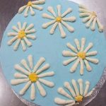 photo of a cake with daisies