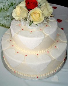 photo of a two tier cake with roses on top