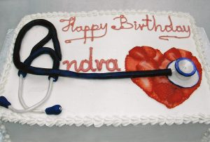 photo of a cake with heart made with strawberries and a stethoscope