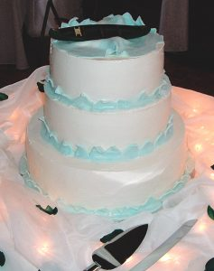 photo of a three tier cake with waves and canoe on top