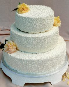 photo of a three tier cake with yellow roses